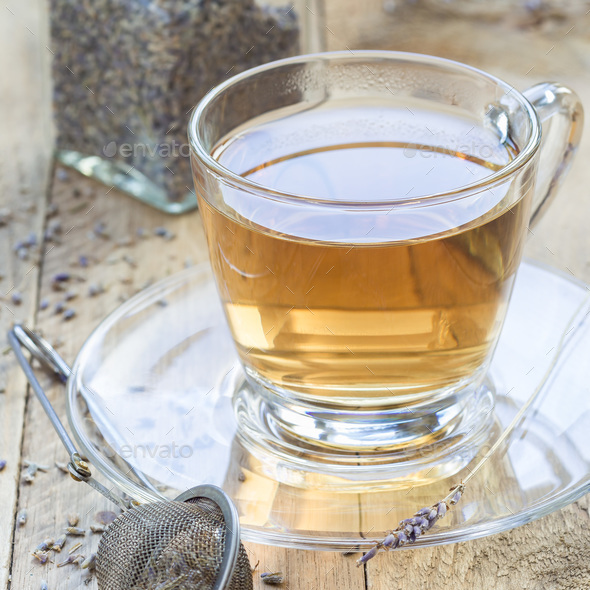 Herbal lavender tea in glass cup with lavender flowers on a wood - Stock Photo - Images