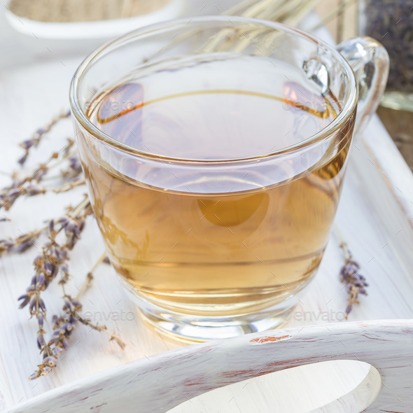 Herbal lavender tea in glass cup with lavender flowers on wooden - Stock Photo - Images