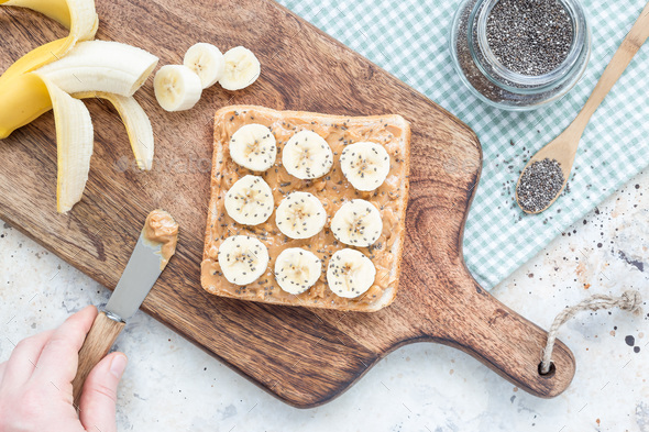 Woman makes healthy sandwich with crunchy peanut butter, banana - Stock Photo - Images