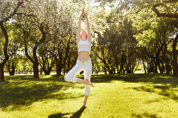 Portrait of smiling young woman stretching at park - Stock Photo - Images