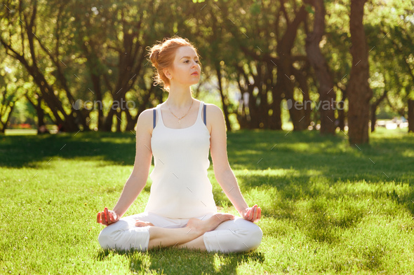 Young girl in lotus pose in the park - Stock Photo - Images