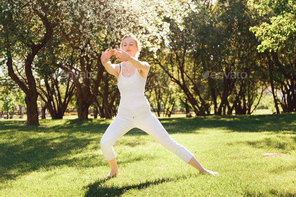 Young female doing exercises at the park. - Stock Photo - Images