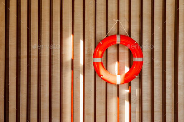 Red lifebuoy hanging on blue wooden wall of a port building - Stock Photo - Images