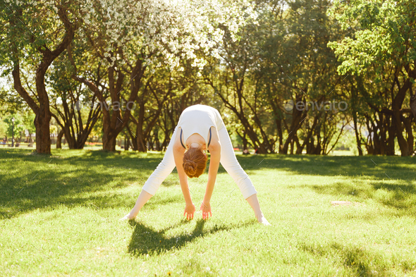 Young female is stretching at the park. - Stock Photo - Images