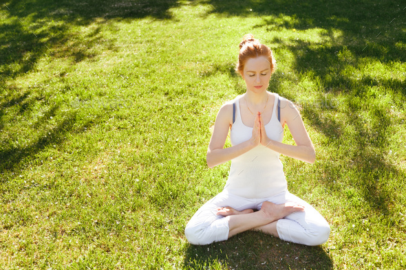 Young red hair woman peacefully meditating in park - Stock Photo - Images
