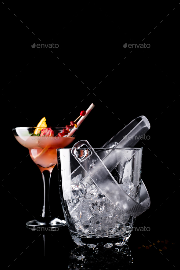 Glass ice bucket and margarita cocktail in glass isolated on black - Stock Photo - Images