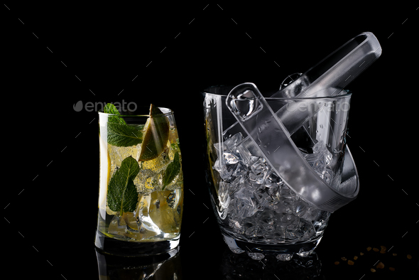 Glass ice bucket and mohito cocktail in glass isolated on black - Stock Photo - Images