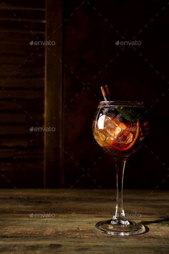 Red berry summer cocktail with brown sugar, blueberries and ice on dark wooden backgorund - Stock Photo - Images