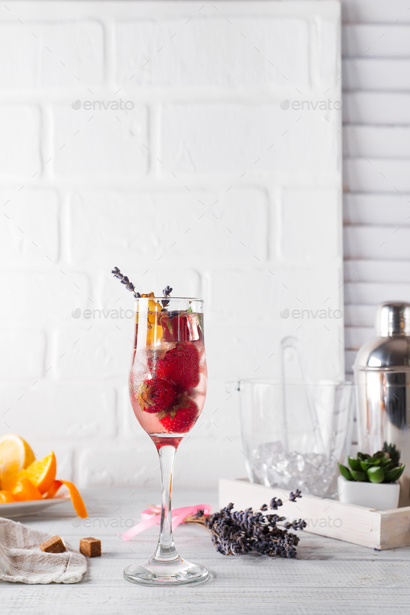 Refreshing cocktail with champagne and cranberry with ice, ginger and lavender on wooden background - Stock Photo - Images