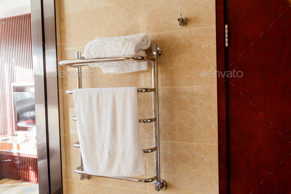 Modern heated towel rail on tiled bathroom wall. - Stock Photo - Images
