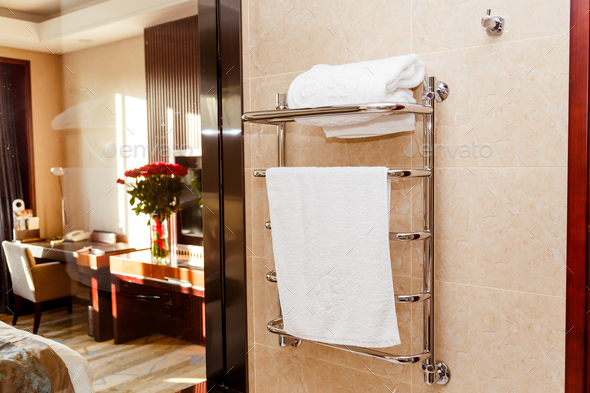 Modern heated towel rail on tiled in hotel - Stock Photo - Images