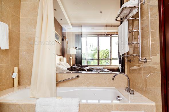 Hotel bathroom interior with window and bathtub. - Stock Photo - Images