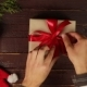 Top View Man Unwrapping Christmas Presents at Wooden Desk Hands From Above - VideoHive Item for Sale