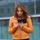Attractive Woman in Yellow Jacket Using Mobile Phone Outdoor in the City - VideoHive Item for Sale
