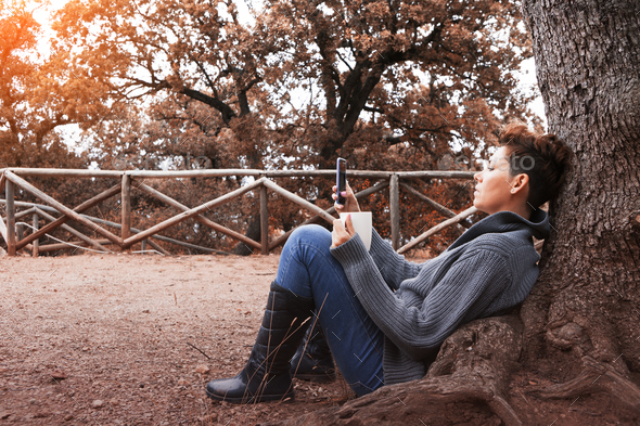 Woman uses technology in autumn forest - Stock Photo - Images