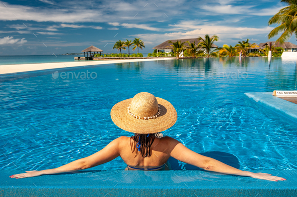 Woman with hat at beach pool in Maldives - Stock Photo - Images