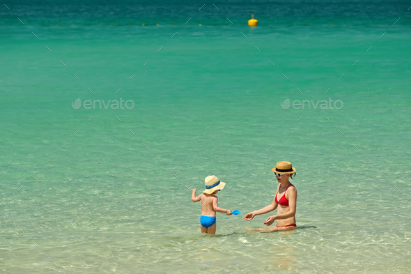 Toddler boy on beach with mother - Stock Photo - Images