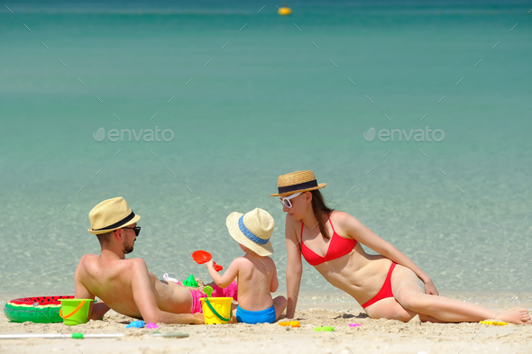 Family on beach. Toddler playing with mother and father. - Stock Photo - Images