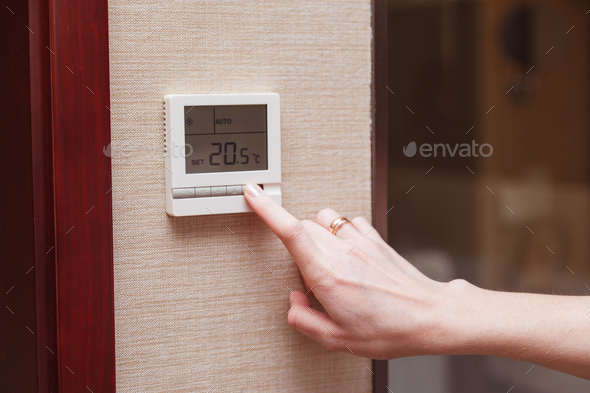 Woman switching a digital thermostat. - Stock Photo - Images