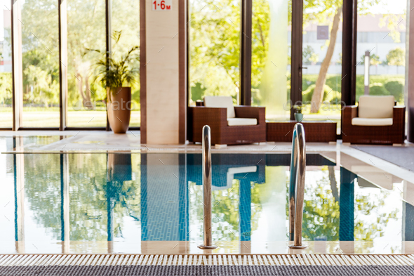 Grab bars ladder in the blue swimming pool - Stock Photo - Images
