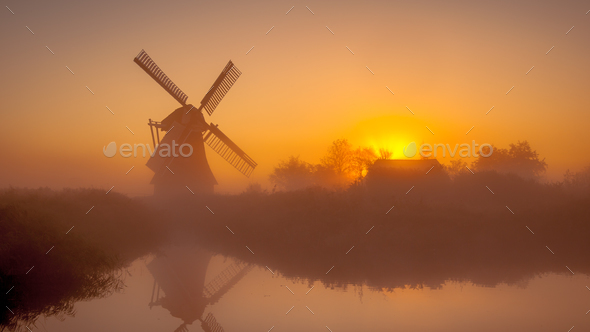 Historic dutch windmill along a canal - Stock Photo - Images