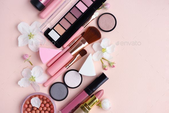 Makeup brush and decorative cosmetics with apple blossom on pink - Stock Photo - Images