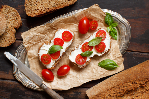 Bruschetta with cream cheese, cherry tomatoes and basil - Stock Photo - Images