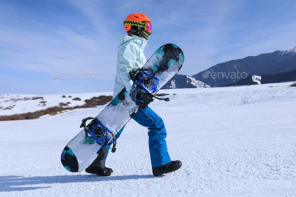 Snowboarder walking on alpine mountain slope - Stock Photo - Images