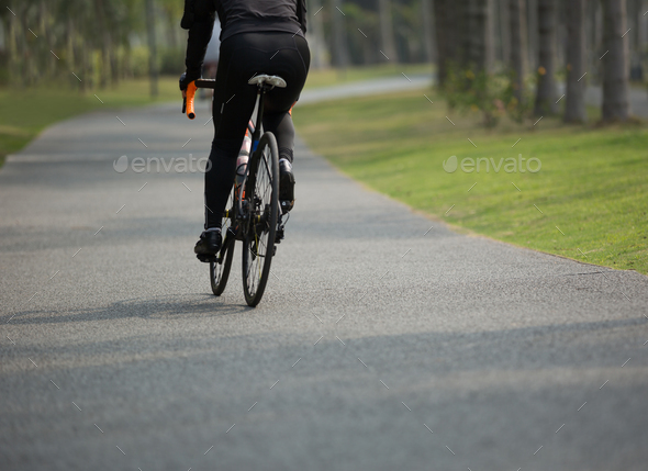 Woman cycling in tropical forest - Stock Photo - Images