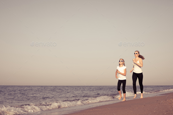 Mother and daughter running on the beach at the day time. - Stock Photo - Images