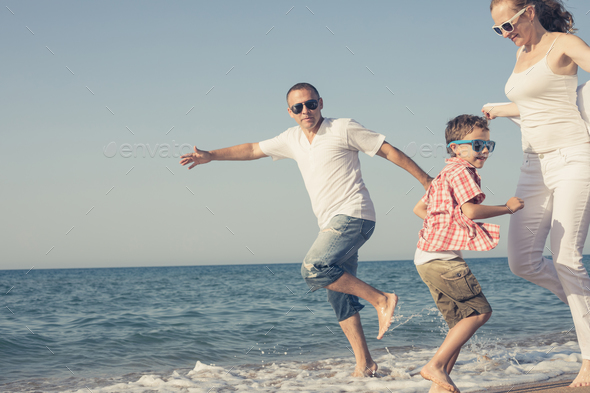 Happy family running on the beach at the day time. - Stock Photo - Images