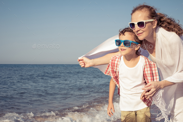 Mother and son standing on the beach at the day time. - Stock Photo - Images