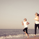 Mother and daughter running on the beach at the day time. - PhotoDune Item for Sale