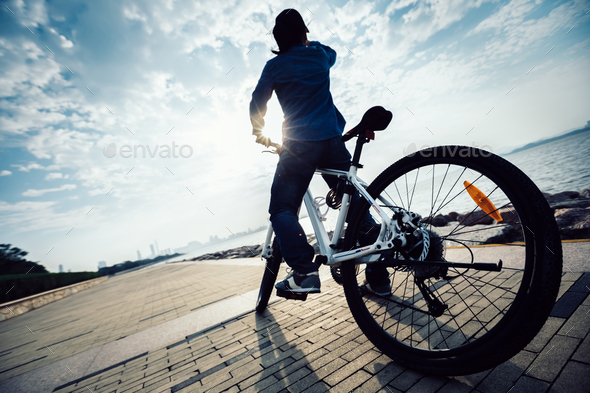 Cyclist looking at the sunrise on seaside - Stock Photo - Images