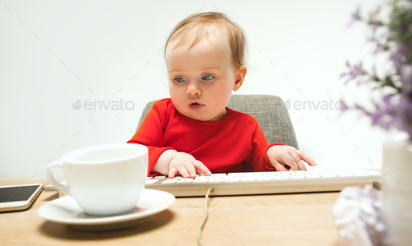 Happy child baby girl toddler sitting with keyboard of computer isolated on a white background - Stock Photo - Images