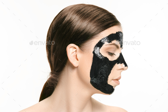 Young beautiful woman applying a mask for the face of the therapeutic black mud. Spa treatment - Stock Photo - Images