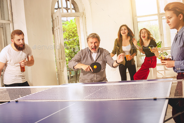 Group of happy young friends playing ping pong table tennis - Stock Photo - Images