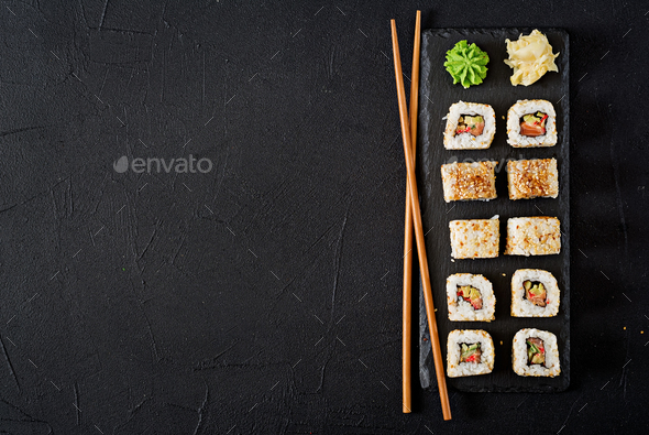 Traditional Japanese food - sushi, rolls and chopsticks for sushi on a dark background. Top view - Stock Photo - Images