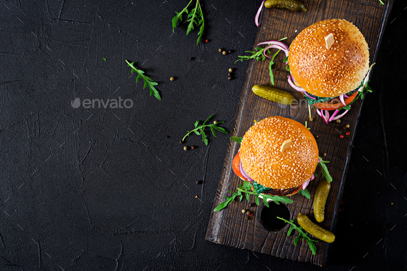 Big sandwich - hamburger burger with beef,  tomato, basil cheese and arugula. Top view. Flat lay - Stock Photo - Images