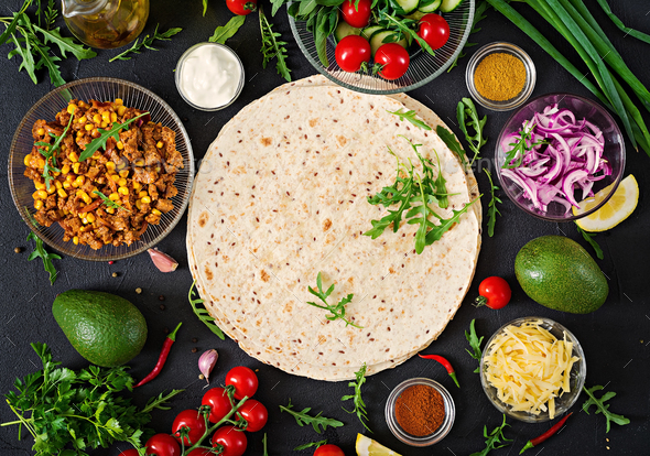 Ingredients for burritos wraps with beef and vegetables on black background - Stock Photo - Images