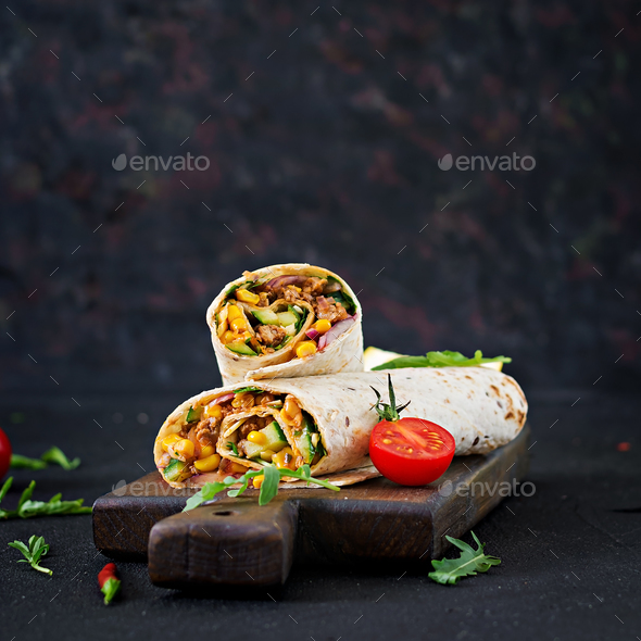 Burritos wraps with beef and vegetables on  black background. Beef burrito, mexican food. - Stock Photo - Images