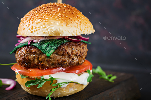 Big sandwich - hamburger burger with beef,  tomato, basil cheese and arugula. - Stock Photo - Images