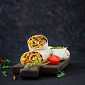 Burritos wraps with beef and vegetables on  black background. Beef burrito, mexican food. - PhotoDune Item for Sale