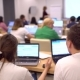 Group of Female and Male Students Are Sitting in a College Classroom and Looking at a Laptop - VideoHive Item for Sale