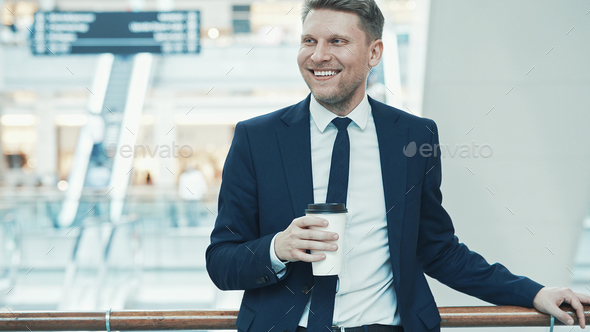 Smiling businessman in suit with coffee - Stock Photo - Images