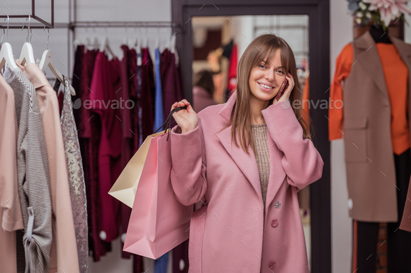 Smiling girl with shopping bags and a phone - Stock Photo - Images