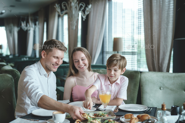 Happy family in a restaurant - Stock Photo - Images