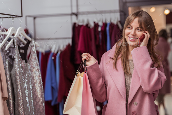 Smiling girl with shopping bags in the shop - Stock Photo - Images