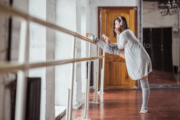 Young ballerina with headphones on training in studio - Stock Photo - Images