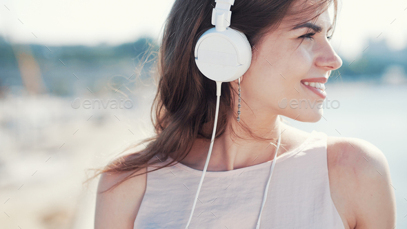 Smiling young girl listen to music outdoors - Stock Photo - Images